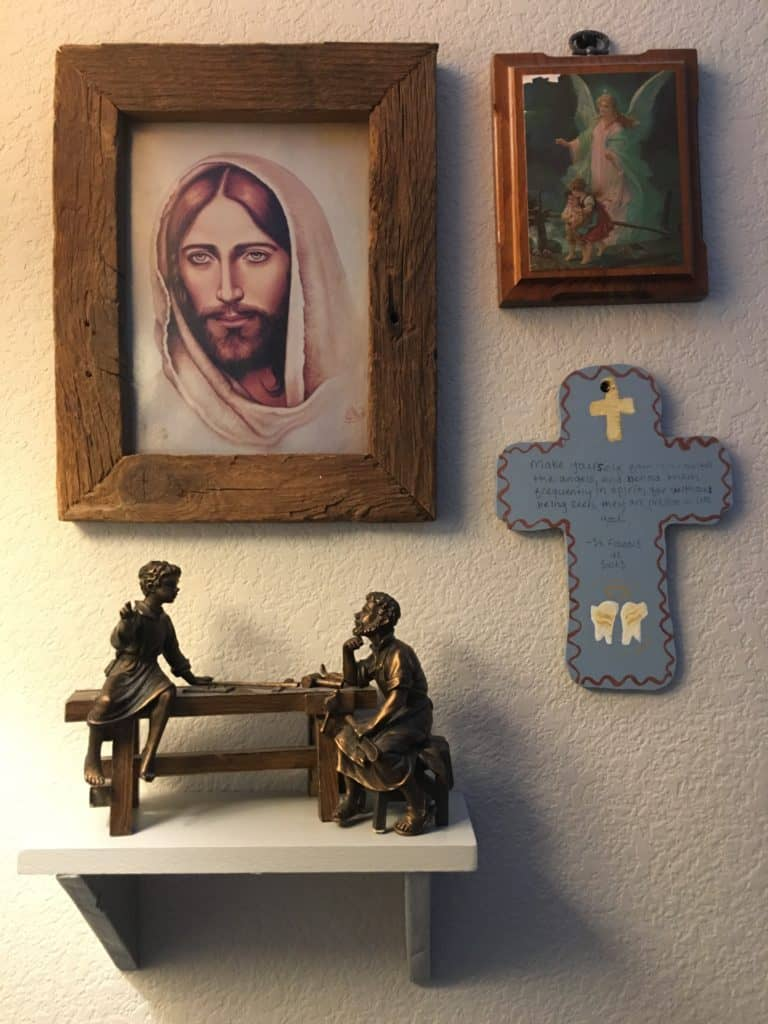 Image: wall display with Jesus, Guardian Angel, shelf and cross.