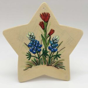 Image: star-shaped wood piece painted with bluebonnets and red paintbrush.
