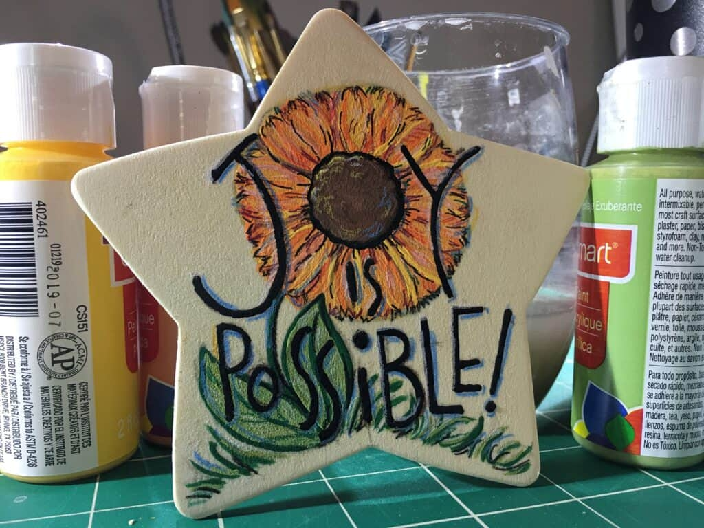 "Image: painted wood star with sunflower and text ""Joy is possible."""