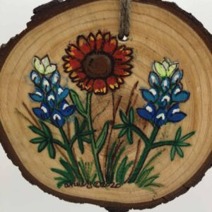 Image: wood circle with bluebonnets and Indian blanket.